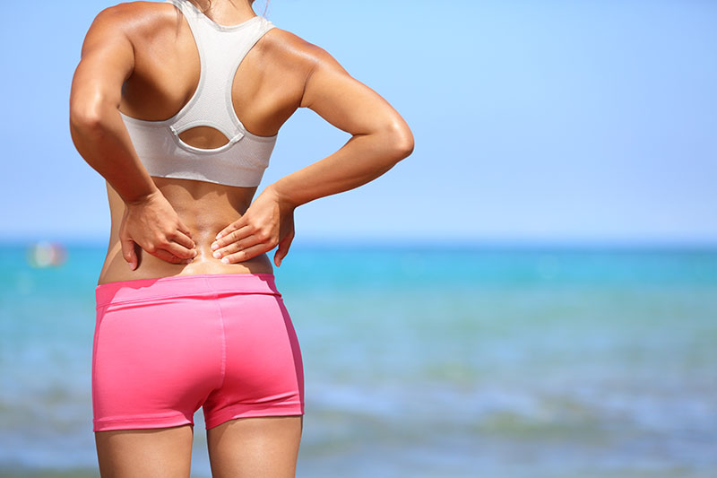 Woman holds aching back | LipoLaser of South Jersey