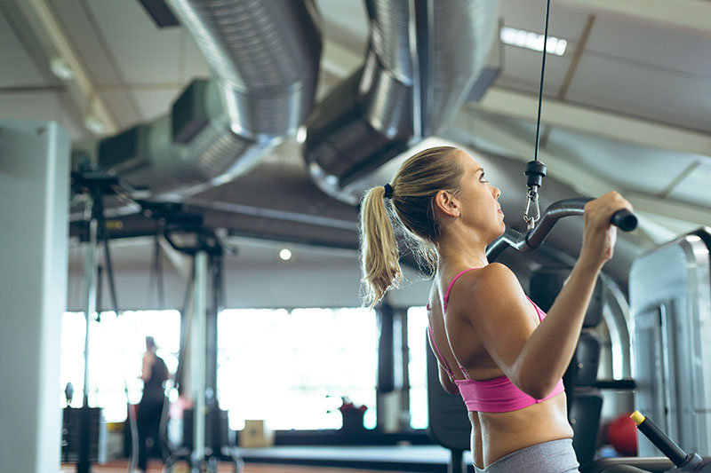 Woman who is considering Emsculpt working out at Gym